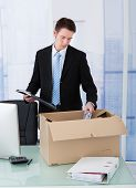 Businessman Collecting Office Supply In Cardboard Box At Desk