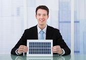 Confident Businessman Holding Solar Panel At Desk