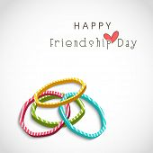 Colorful pearl bangles on grey background for Happy Friendship Day celebrations.