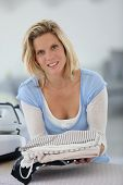 Smiling young housekeeper woman holding pile of clothes