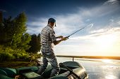 foto of boat  - Mature man fishing from the boat on the pond at sunset - JPG