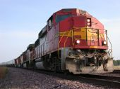 foto of locomotive  - A red diesel locomotive pulls a freight train on the mail track - JPG