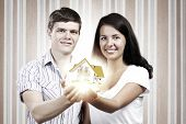 Happy young couple holding model of house on palms