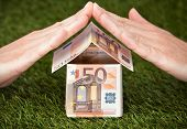 Businessman's Hands Protecting Euro House On Grassy Land