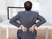 Businessman Suffering From Backache While Sitting At Desk