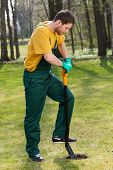 foto of dungarees  - Side view of a strong man in dungarees digging in garden - JPG