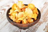 stock photo of chanterelle mushroom  - Chanterelle mushroom in clay bowl on wooden background
