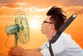 stock photo of heatwave  - the heat wave is comingbusiness man holding a electric fan - JPG
