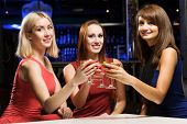 Three elegant ladies with cocktails at night club