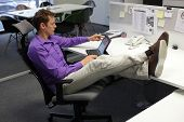Young businessman caucasian in his office working with tablet - relaxed sitting position with legs on desk
