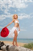 Young woman in white bikini holding sarong on windy beach
