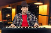 Photo Of Young Cowboy Playing The Digital Piano At Pub