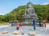 SOKCHO, SOUTH KOREA - October 20, 2013: Prayers at giant statue of Buddha in the Sinheungsa Temple in Seoraksan National Park, South korea