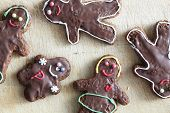 Handmade decorated gingerbread people lying on wooden table. Christmas