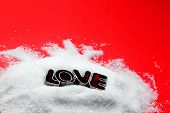 Love text message from cookie form letters on sugar and red background. Valentines Day theme, greeting card.