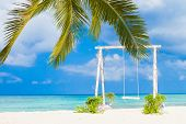 wedding swing decorated with flowers on tropical sand beach, outdoor beach wedding setup