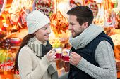 picture of hot couple  - Romantic young couple drinking hot wine punch claret on christmas market - JPG