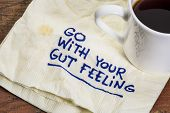 go with your gut feeling - advice or motivational reminder  on a napkin with cup of espresso coffee