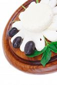 diet products : salted greek feta white cheese with olives and basil leaves sliced on wood isolated over white background
