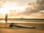 Surfboard and young couple  at sunset on Bali island, Indonesia