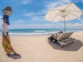 Lady in white hat sitting in chaise longue in Bali with old beach seller passing by
