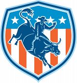 foto of bull-riding  - Illustration of rodeo cowboy riding bucking bull set inside shield crest with american stars and stripes flag in the background done in retro style - JPG