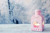 Lantern on wooden table on winter background
