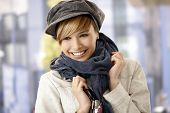 Portrait of happy young woman wearing scarf and hat, smiling.