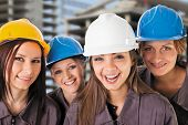 Smiling women construction team with protective clothing. Isolated with work path.
