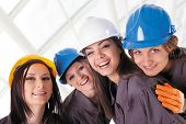 picture of work crew  - Young female construction workers with protective clothes and helmets - JPG