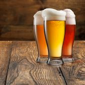 Different beer in glasses on wooden background