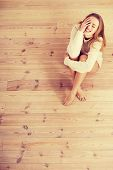 Beautiful carefree young casual woman sitting on the wooden floor.
