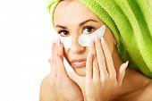 Caucasian woman with gel eye mask touching face.