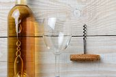 High angle closeup of a bottle of white wine next to a wineglass and corkscrew on a whitewashed rustic table. Horizontal format.