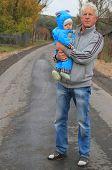 grandfather and his grandchild in rural landscape