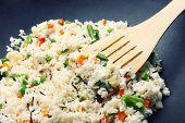 Tasty rice preparing in wok, close-up