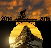Cyclist riding across the bridge at sunset. In the background Matterhorn. Forward to the New Year 2015