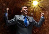 Young joyful businessman with hands up celebrating success
