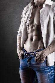 stock photo of dark-skin  - Sexy young man in shirt on a dark background - JPG