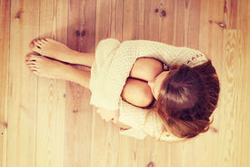 stock photo of shy woman  - Beautiful caucasian woman is sitting on the floor - JPG