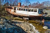 image of wrecking  - Old and rusty shipwreck pulled out of the water and set on land - JPG