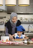 stock photo of hijabs  - Moslem woman wearing hijab teaching her daughter make halal food - JPG