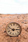 stock photo of analog clock  - Classic Analog Clock In The Sand On The Rock Desert - JPG