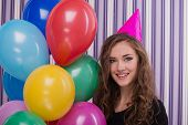 image of birthday hat  - Photo of happy young woman looking at camera and smiling. Woman wearing birthday hat and holding colourful balloons. Concept for happy birthday