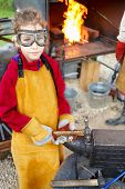 image of anvil  - smith girl in goggles and apron with hammer and anvil - JPG