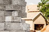 picture of urbanisation  - A close up view of stacked grey concrete bricks infront of an unfinished house - JPG