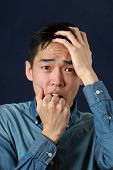 stock photo of disappointed  - Disappointed young Asian man looking at camera - JPG