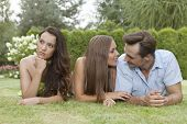 foto of ignorant  - Loving young couple ignoring female friend in park - JPG