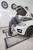 stock photo of car repair shop  - Full length side view of male automobile mechanic repairing car engine in repair shop - JPG