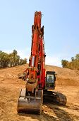 image of track-hoe  - Large track hoe excavator removing top soil and dirt from a new commercial development construction site - JPG